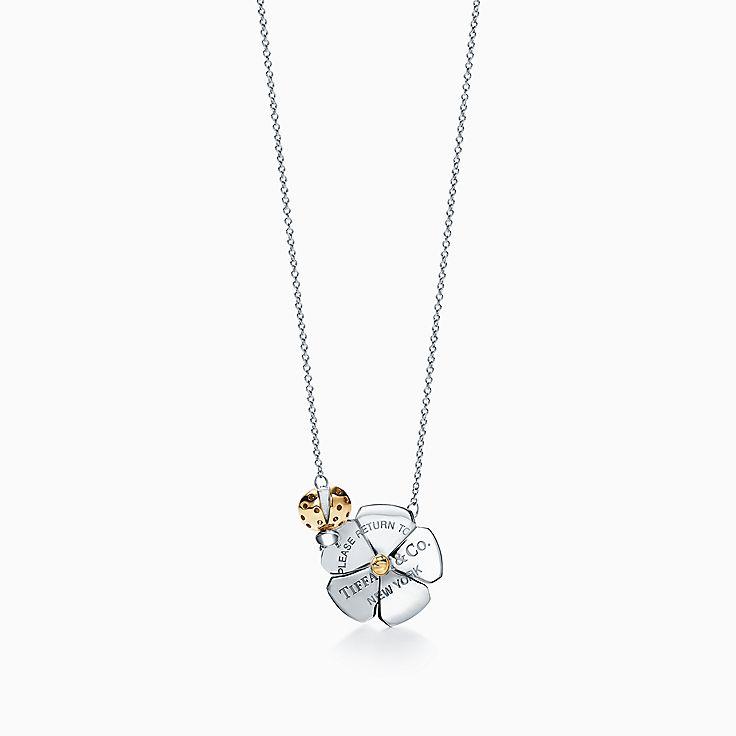Return to Tiffany™ Love Bugs:Colgante con mariquita y flor en plata de ley y oro de 18 ct
