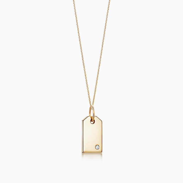 tiffany charms tag in 18k gold with a diamond mini